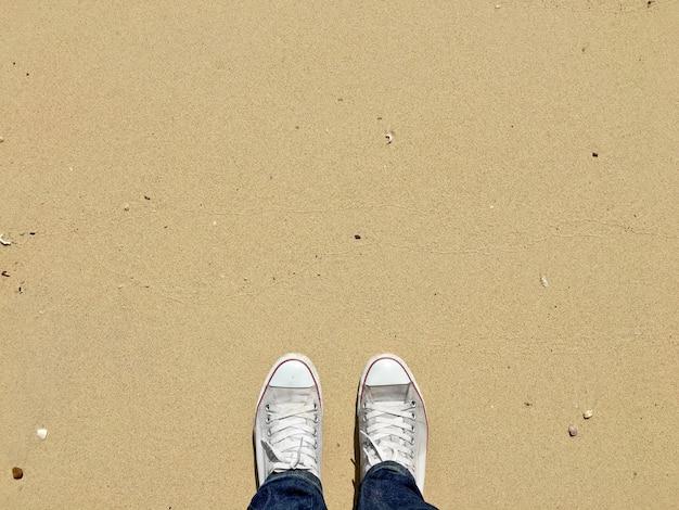 Vue de dessus des chaussures blanches sur fond de texture de plage de sable