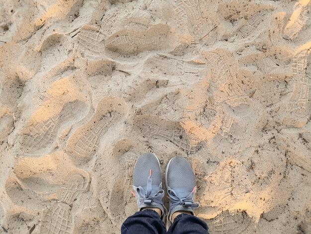 Vue de dessus des chaussures sur la plage de sable tropicale