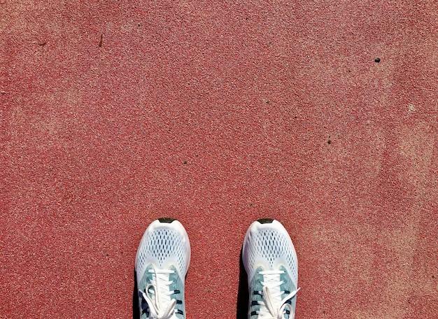 Vue de dessus des chaussures utilisées pour les hommes qui courent sur le groud rouge