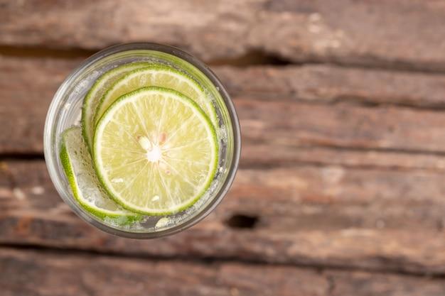 Vue de dessus de la chaux verte tranchée dans l'eau gazéifiée et le verre sur la table en bois