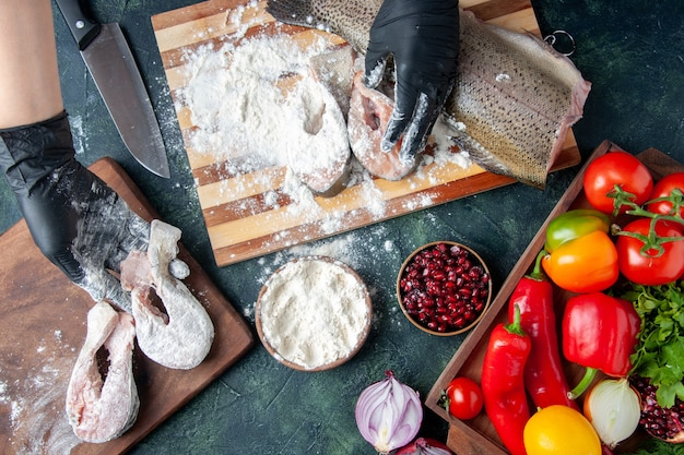 Vue de dessus chef couvrant des tranches de poisson cru avec de la farine de légumes frais sur un bol de farine de planche de bois sur la table de la cuisine