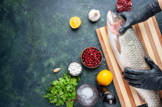 Vue de dessus chef avec des gants noirs tenant du poisson cru sur planche de bois moulin à poivre graines de grenade dans un bol sur l'espace libre de la table