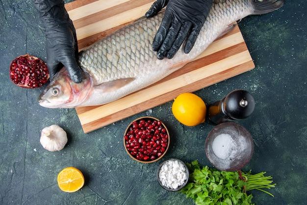 Vue de dessus chef avec des gants noirs tenant du poisson cru sur une planche à découper des graines de grenade de moulin à poivre dans un bol sur un espace libre de table