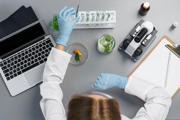 Vue de dessus de la chercheuse dans le laboratoire avec ordinateur portable