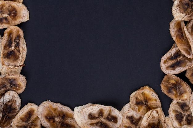 Vue de dessus des chips de banane séchées isolé sur fond noir avec copie espace