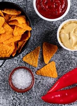 Vue de dessus des chips dans une poêle en métal noir et des épices avec des saucisses dans des bols sur la pierre blanche verticale