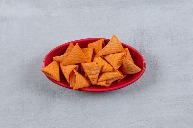 Vue de dessus de chips épicées dans un bol rouge.