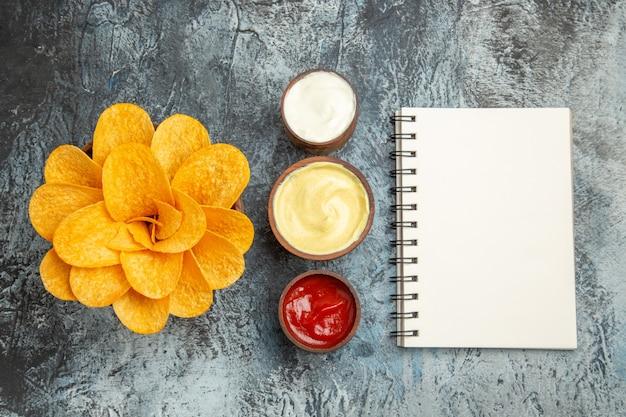 Vue de dessus de chips maison décorées en forme de fleur et de sel avec de la mayonnaise au ketchup et ordinateur portable sur table grise