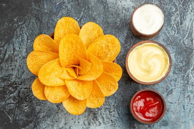 Vue de dessus de chips maison décorées en forme de fleur et de sel avec de la mayonnaise au ketchup sur table grise