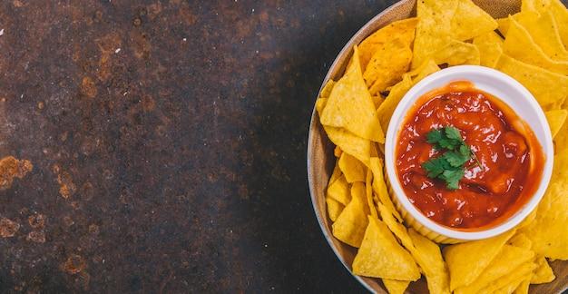 Vue de dessus des chips de nachos mexicains avec une sauce salsa épicée dans un bol