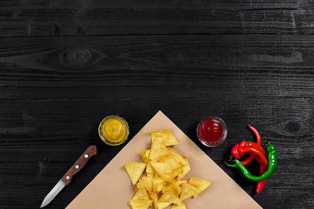 Vue de dessus des chips tortilla avec sauce et piment rouge sur fond de bois noir