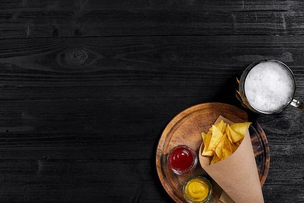 Vue de dessus des chips tortilla avec sauce verre de bière sur fond de bois noir