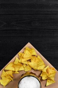 Vue de dessus des chips tortilla et verre de bière sur fond de bois noir