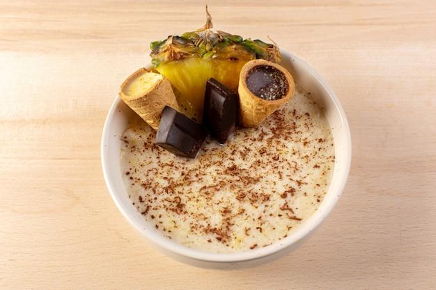 Une vue de dessus choco dessert brun avec une tranche d'ananas barres de chocolat crème glacée à l'intérieur de la plaque blanche sur la crème