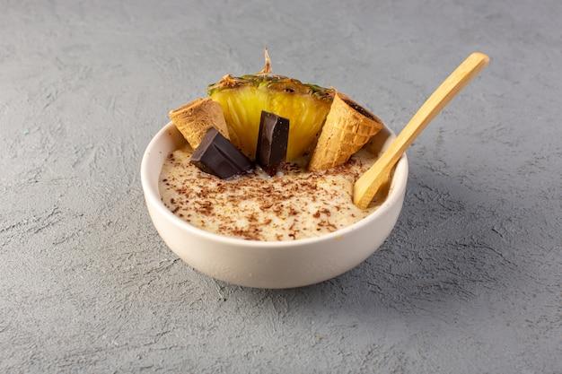 Une vue de dessus choco dessert brun avec une tranche d'ananas barres de chocolat crème glacée à l'intérieur de la plaque blanche sur le gris