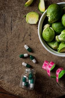 Vue de dessus des choux de bruxelles avec des médicaments sur la table