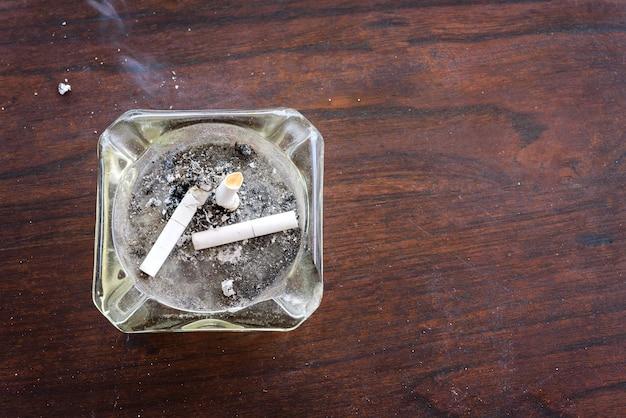 Vue de dessus de cigarettes bout à bout dans le cendrier sur une table en bois avec de la fumée de cigarette