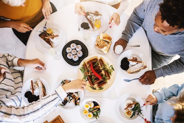 Vue de dessus de cinq amis multiculturels assis à table à manger et déjeuner sain.