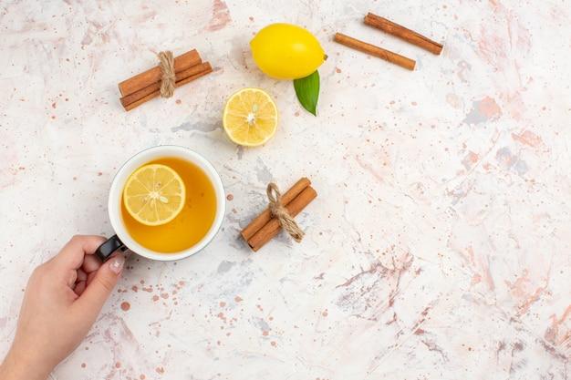 Vue de dessus citron frais coupé citron cannelle bâtons une tasse de thé au citron dans une main féminine sur l'espace libre de surface isolé lumineux
