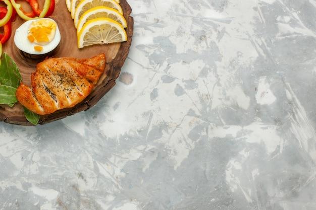 Vue de dessus citron et légumes avec petit pain sur un bureau blanc léger légumes repas repas déjeuner