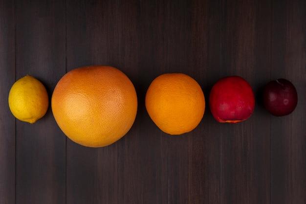 Vue de dessus citron avec pamplemousse orange pêche et prune sur fond de bois
