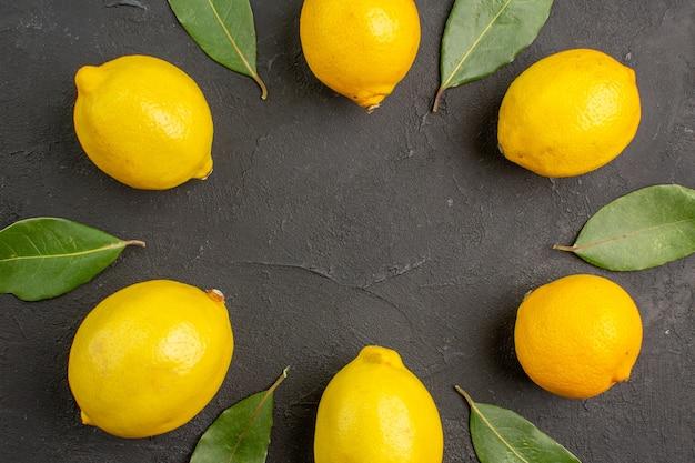 Vue de dessus citrons aigres frais bordés sur table sombre, citron vert citron vert