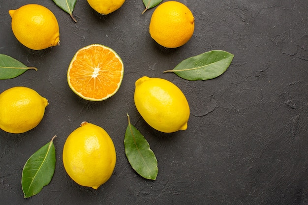 Vue de dessus citrons aigres frais bordés sur table sombre, fruits jaune citron vert citron