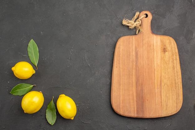 Vue de dessus citrons aigres frais avec des feuilles sur la table sombre fruits citron vert citron jaune
