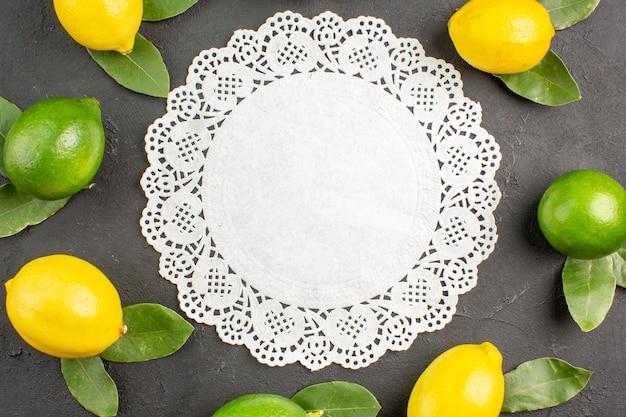 Vue de dessus citrons aigres frais sur la table gris foncé citron vert citron
