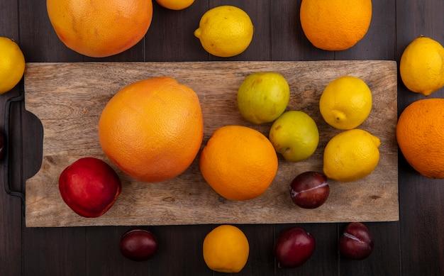 Vue de dessus citrons aux oranges prunes pêche et pamplemousse sur une planche à découper sur un fond en bois