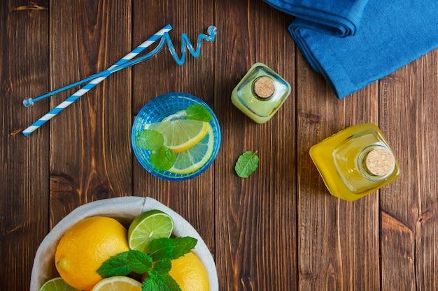 Vue de dessus citrons dans le panier avec un chiffon bleu, un couteau en bois et une bouteille de jus, des pailles sur une surface en bois.