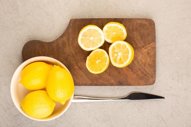 Une vue de dessus des citrons frais aigre mûrs entiers et coupés en tranches d'agrumes tropicaux jaune vitamine tropicale sur le bureau de la crème