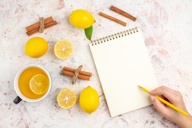 Vue de dessus des citrons frais coupés en bâtons de cannelle citron une tasse de crayon de thé au citron dans un bloc-notes de main féminine sur une surface isolée lumineuse