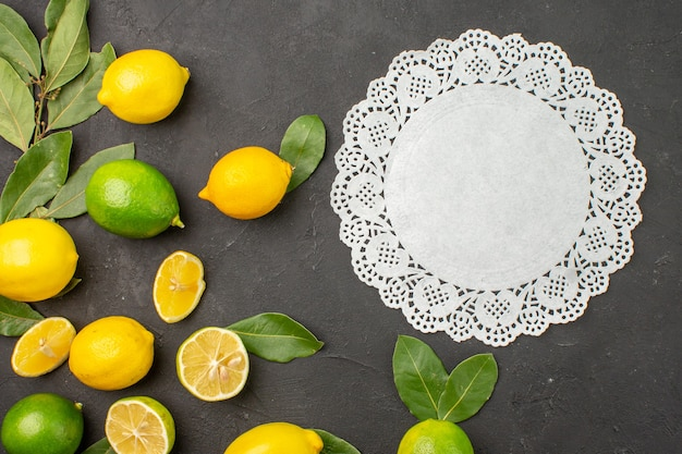 Vue de dessus citrons frais fruits aigres sur la table sombre agrumes citron vert
