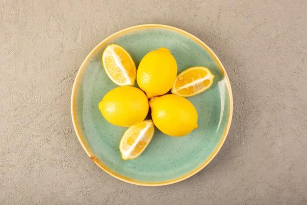 Une vue de dessus les citrons frais jaunes mûrs et juteux entiers et tranchés à l'intérieur de la plaque verte sur le fond gris fruits couleur agrumes