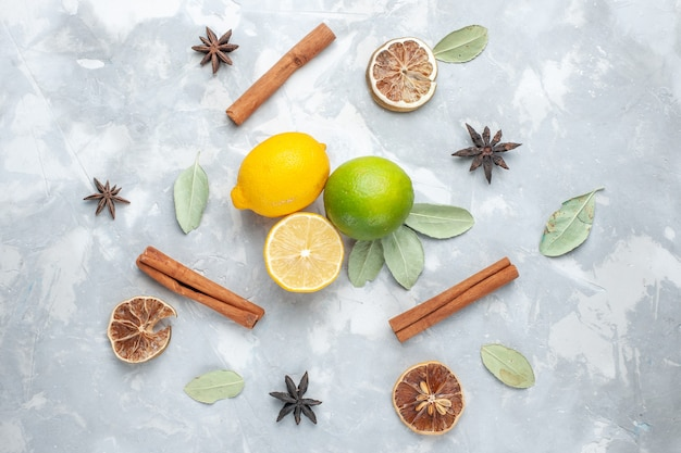 Vue de dessus citrons frais juteux et aigre à la cannelle sur un bureau blanc tropique fruits exotiques agrumes