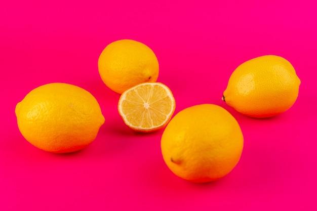 Une vue de dessus des citrons jaunes isolés des citrons mûrs juteux frais sur le fond rose d'agrumes frais