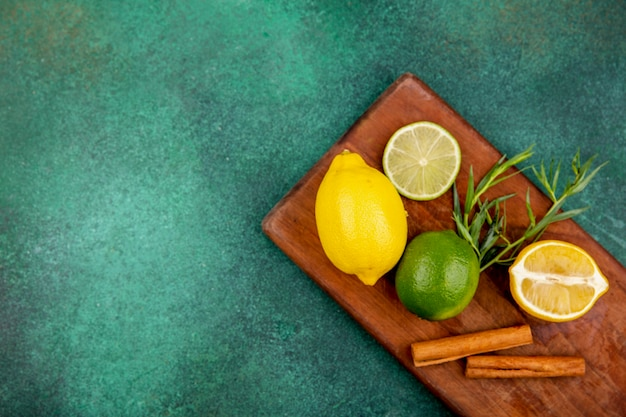 Vue de dessus des citrons jaunes et verts sur une planche de cuisine en bois avec des bâtons de cannelle sur une surface verte