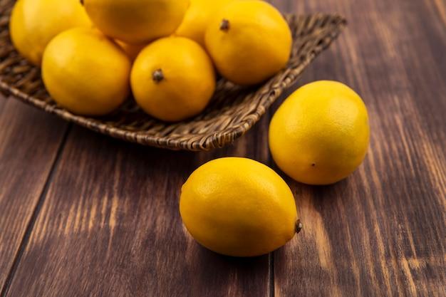 Vue de dessus de citrons sains sur un plateau en osier avec des citrons isolés sur un mur en bois