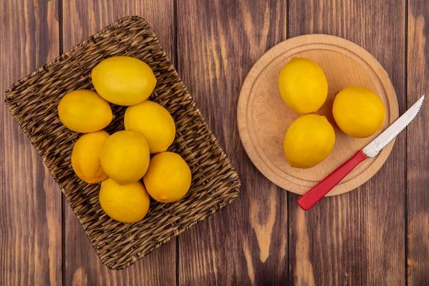 Vue de dessus de citrons sains sur un plateau en osier avec des citrons isolés sur une planche de cuisine en bois avec un couteau sur un mur en bois