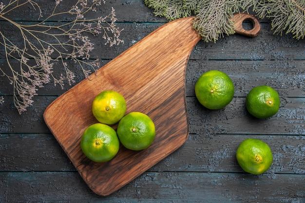Vue de dessus des citrons verts à bord des citrons verts sur une planche à découper sur la table à côté des branches d'arbres et de trois citrons verts