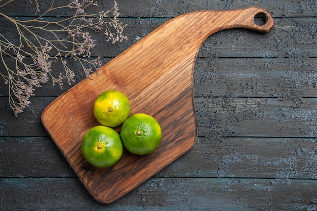 Vue de dessus des citrons verts à bord de trois citrons verts sur une planche à découper sur la table à côté des branches