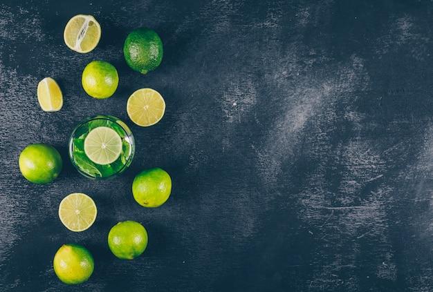 Vue de dessus des citrons verts dans un verre d'eau et autour avec des tranches sur fond texturé noir. espace horizontal pour le texte