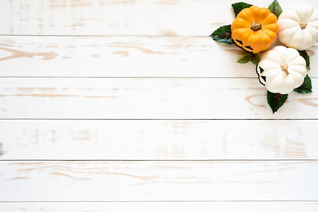 Vue de dessus des citrouilles fantômes blancs et jaunes sur un fond en bois blanc