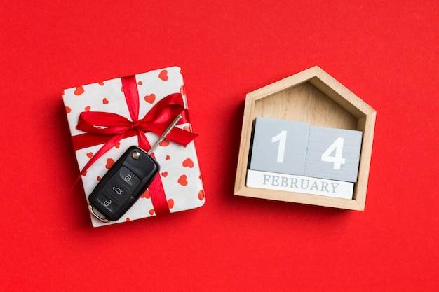 Vue de dessus de la clé de voiture sur une boîte cadeau avec coeurs rouges et calendrier festif