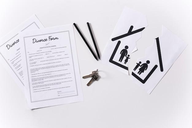 Vue de dessus des clés de la maison avec des formulaires de divorce sur la table