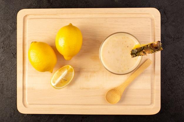 Une vue de dessus cocktail frais boisson rafraîchissante délicieux à l'intérieur d'un petit verre près de bureau de crème en bois avec des citrons jaunes sur l'obscurité