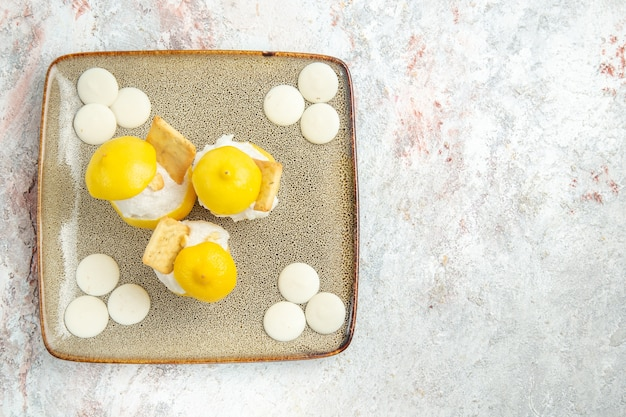 Vue de dessus des cocktails au citron avec des bonbons blancs sur table blanche boire du jus de fruits cocktail