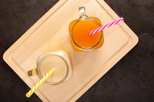 Une vue de dessus des cocktails froids colorés à l'intérieur de canettes en verre avec des pailles colorées sur le bureau en bois crème et sombre