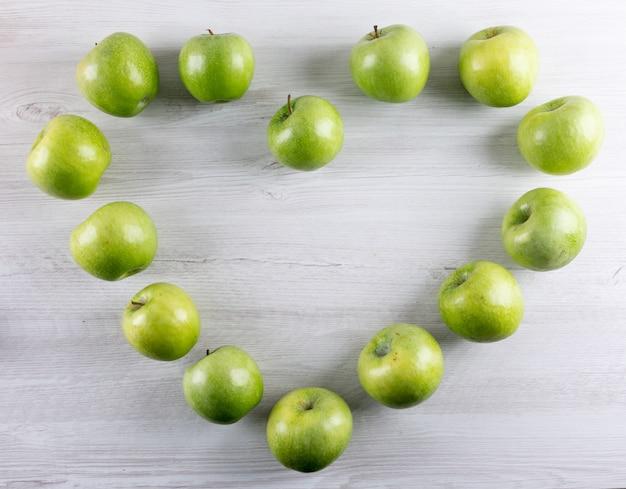 Vue de dessus coeur de pommes vertes sur horizontal en bois blanc
